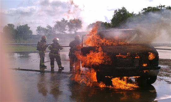 Firefighters fighting a car fire